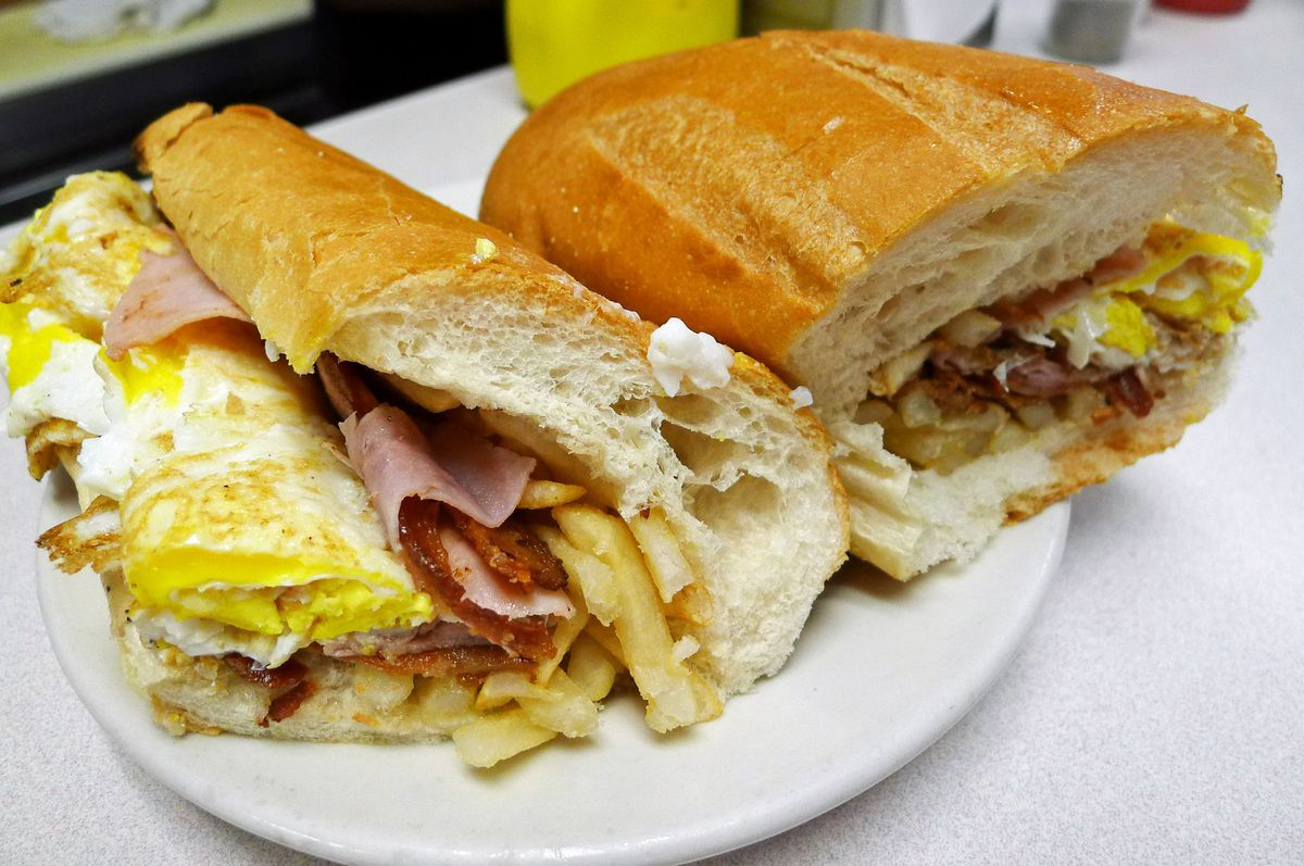 A hero sandwich with eggs, ham, and french fries tumbling out.