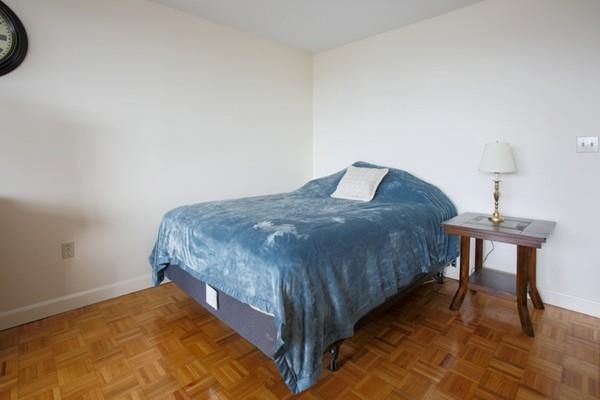 A sparse sleeping area with a bed in a studio apartment.