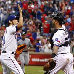 Texas Rangers relief pitcher Koji Uehara, left, celebrates with catcher Mike Napoli (25) after beating the Seattle Mariners 2-1 in a baseball game Sunday, Sep. 16, 2012, in Arlington, Texas.