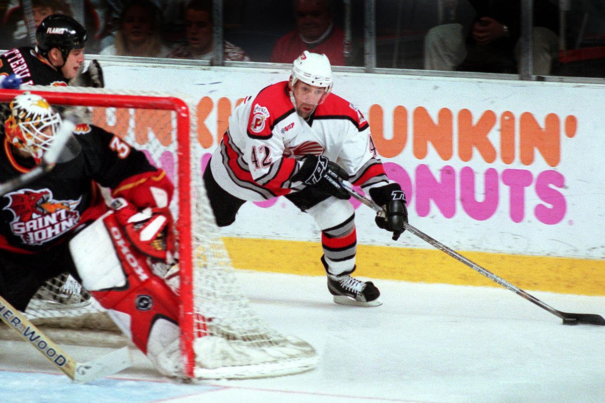 David Emma of the Portland Pirates is followed by Jason Botterill of the St. John Flames as he swing...