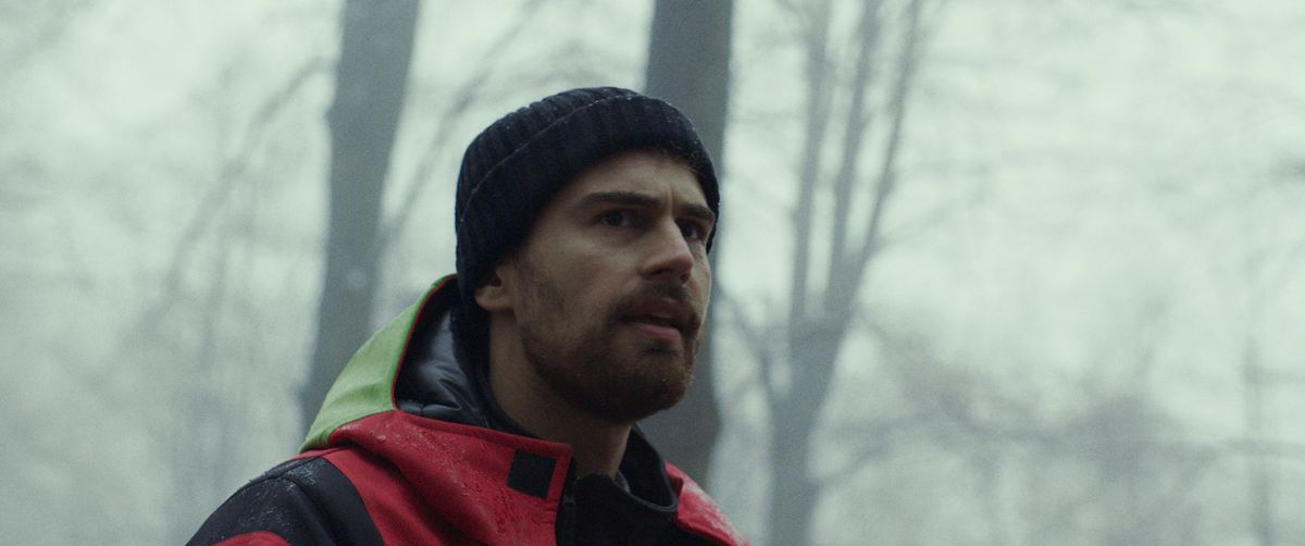 Theo James stands outside in the snow in a knit hat and red jacket in Archive.