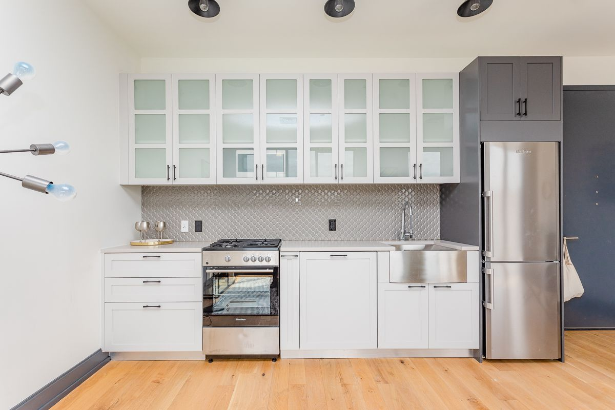 An open kitchen with white cabinetry.