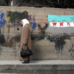 """A Syrian woman and her daughter walk past a wall with a painting of the Syrian revolutionary flag and Arabic writing that reads,""""only al-Arour,"""" the name of an Islamic cleric living in Saudi Arabia who opposes President Bashar Assad, in a neighborhood of Damascus, Syria, Monday, April 2, 2012."""
