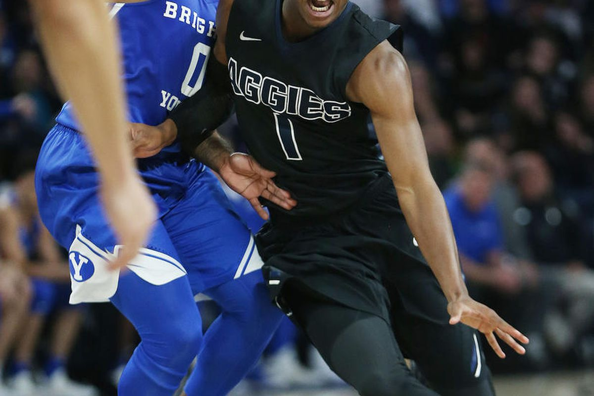 Utah State Aggies guard Koby McEwen (1) drives on Brigham Young Cougars guard Jahshire Hardnett (0) in Logan on Saturday, Dec. 2, 2017. BYU won 75-66.