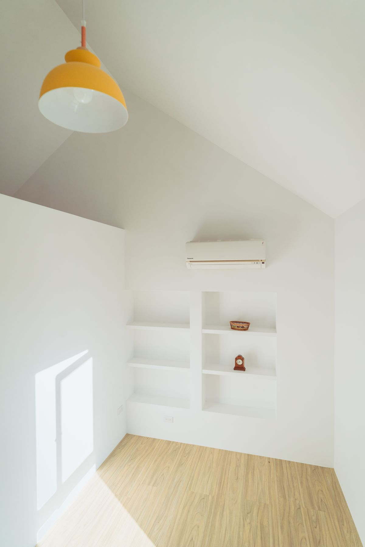 A room with white walls and pale wood floors.