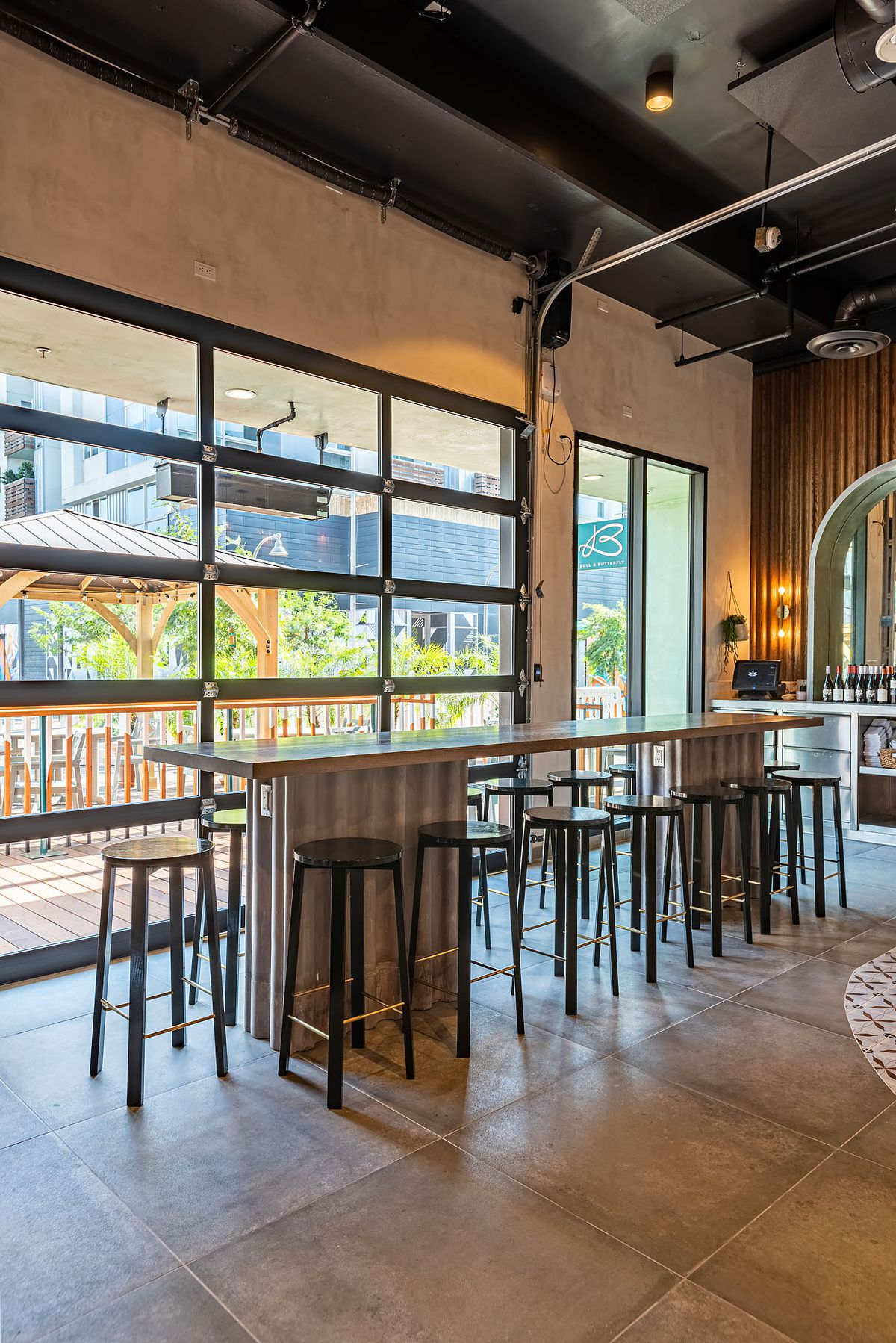 Roll-up doors show communal tables and metal stools.