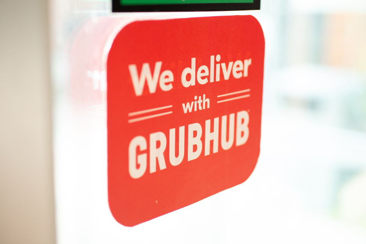 """A sign on a restaurant window reads """"We deliver with Grubhub"""""""