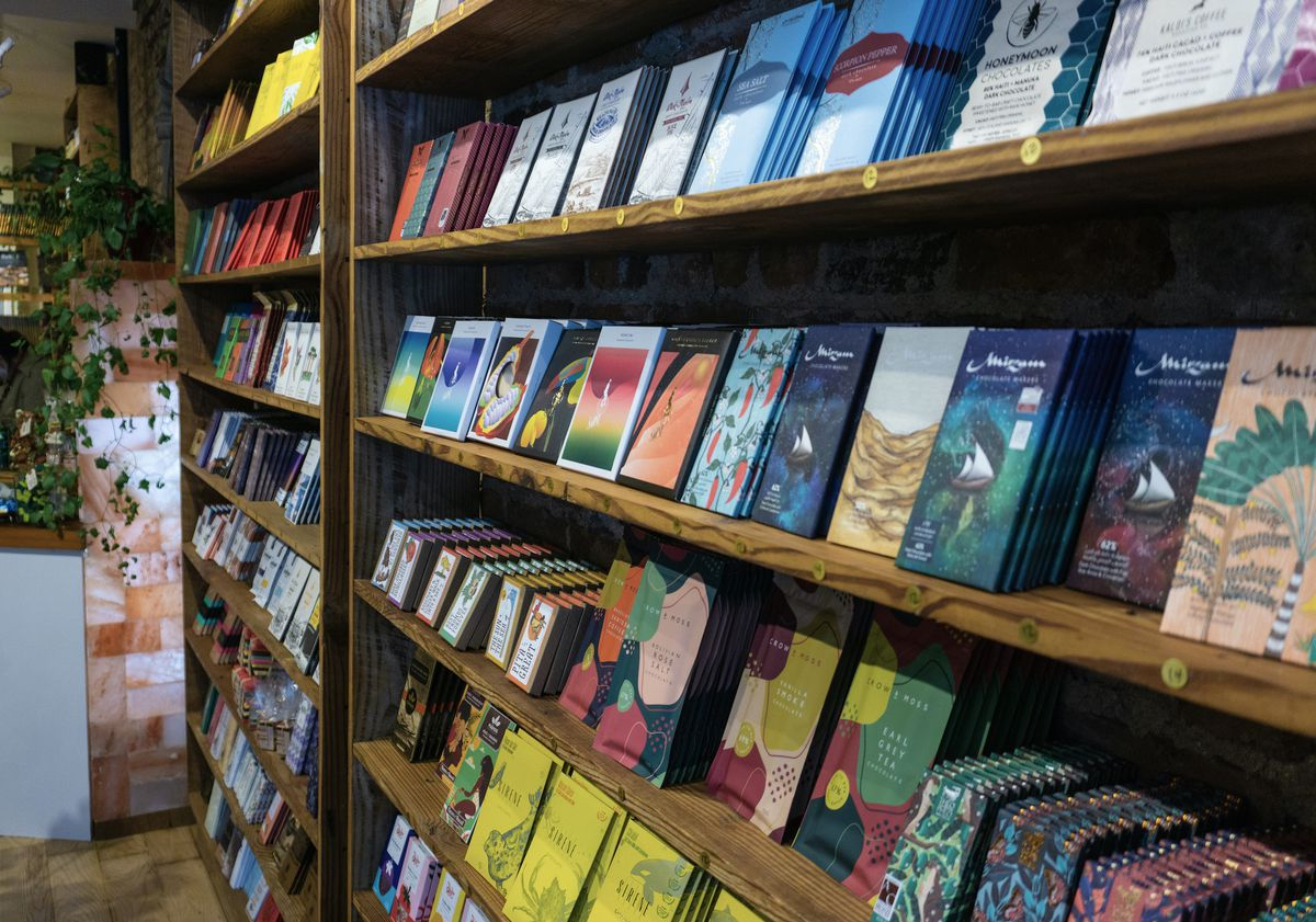 Two bookshelves lined with colorful bars of chocolate.