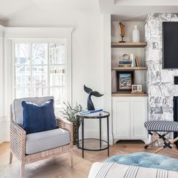 An armchair tucks comfortably into the windowed bay of the living room, space taken from what was part of the original home's porch. Built-in cabinets flank the gas fireplace.
