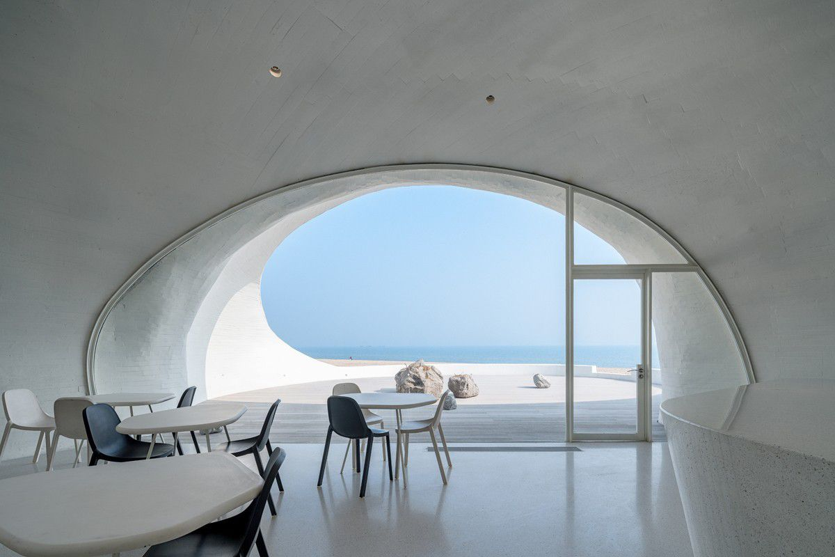 Tables and chairs in front of large oval window
