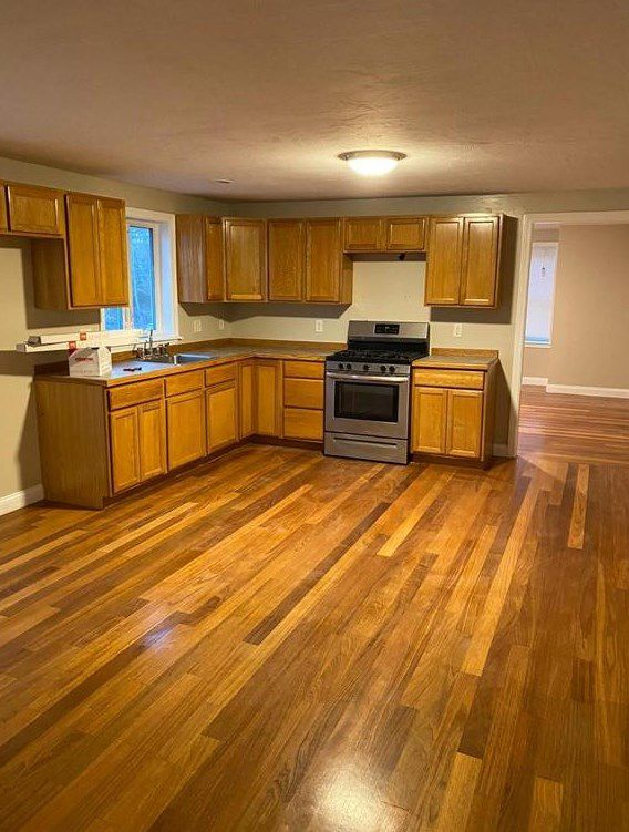 An empty kitchen with two counters meeting at a right angle.