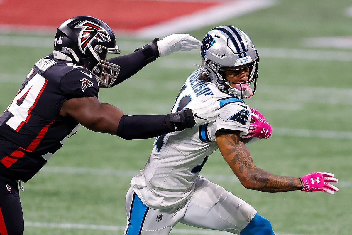 Robby Anderson #11 of the Carolina Panthers attempts to break a tackle by Foyesade Oluokun #54 of the Atlanta Falcons during the first half at Mercedes-Benz Stadium on October 11, 2020 in Atlanta, Georgia.