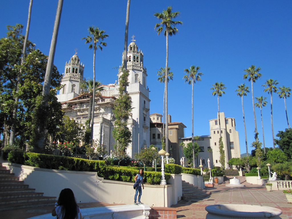The exterior of Hearst Castle. The facade is white and there are multiple towers. There are palm trees in front of the building.