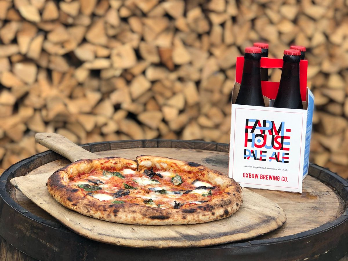 A four-pack of beer bottles beside a full pizza on a wooden pizza paddle, all sitting on a barrel in front of a wood pile