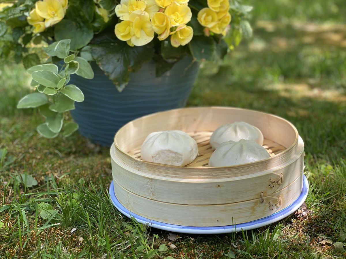 Prime Food steam roasted pork buns sit on a steamer tray next to a pot of yellow flowers in a garden