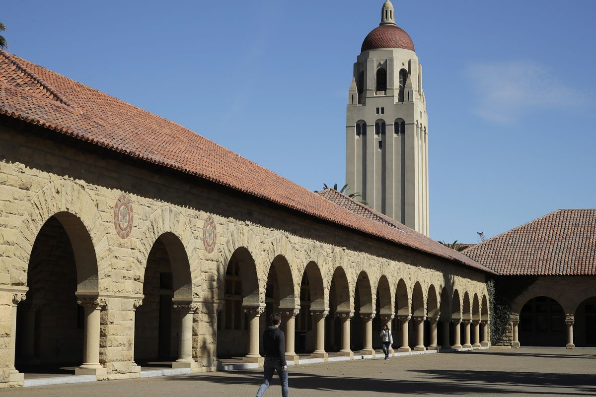 People walk on the Stanford University campus beneath Hoover Tower Thursday, March 14, 2019, in Santa Clara, Calif. In the first lawsuit to come out of the college bribery scandal, several students are suing Yale, Georgetown, Stanford and other schools in