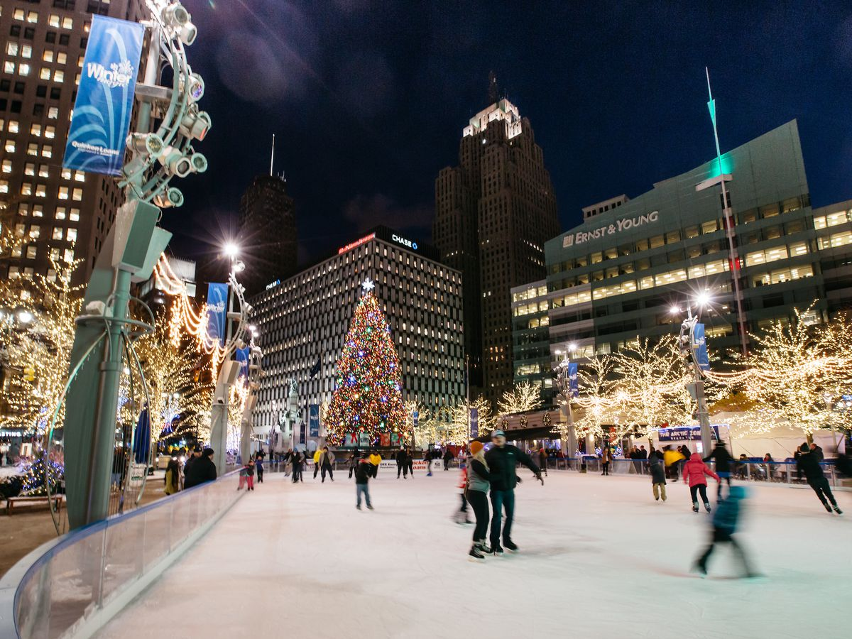 Kids and parents skate on an ice rink downtown at night. Nearby trees are strung with festive lights.