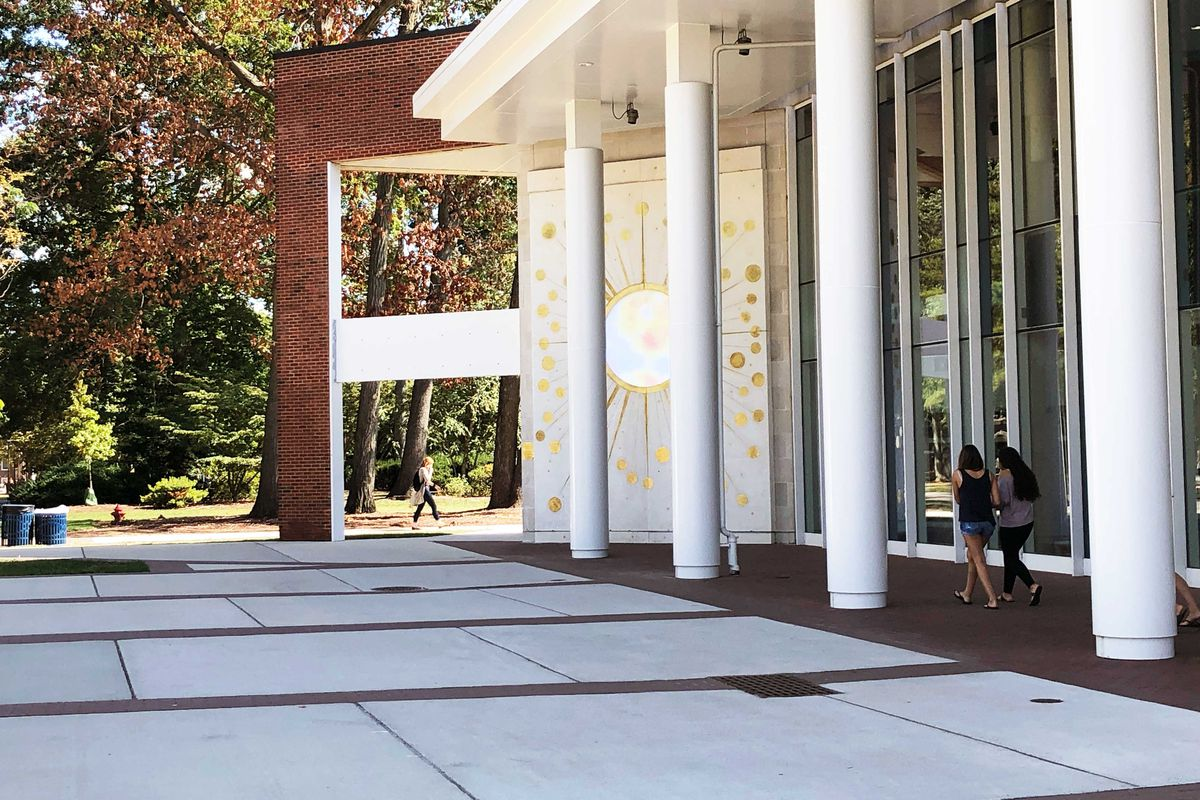 Students walk by pillars outside the Brower Student Center on the TCNJ campus, with trees in the background.