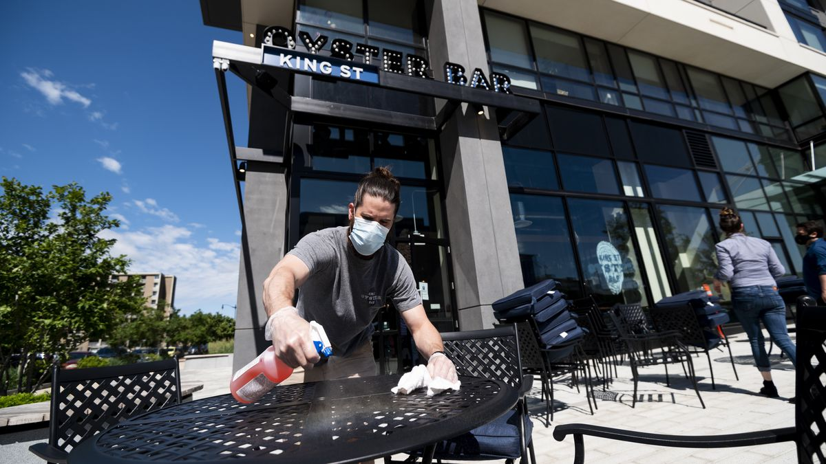 Head bartender Sean Hughes cleans a table as the King Street Oyster Bar restaurant in NoMa