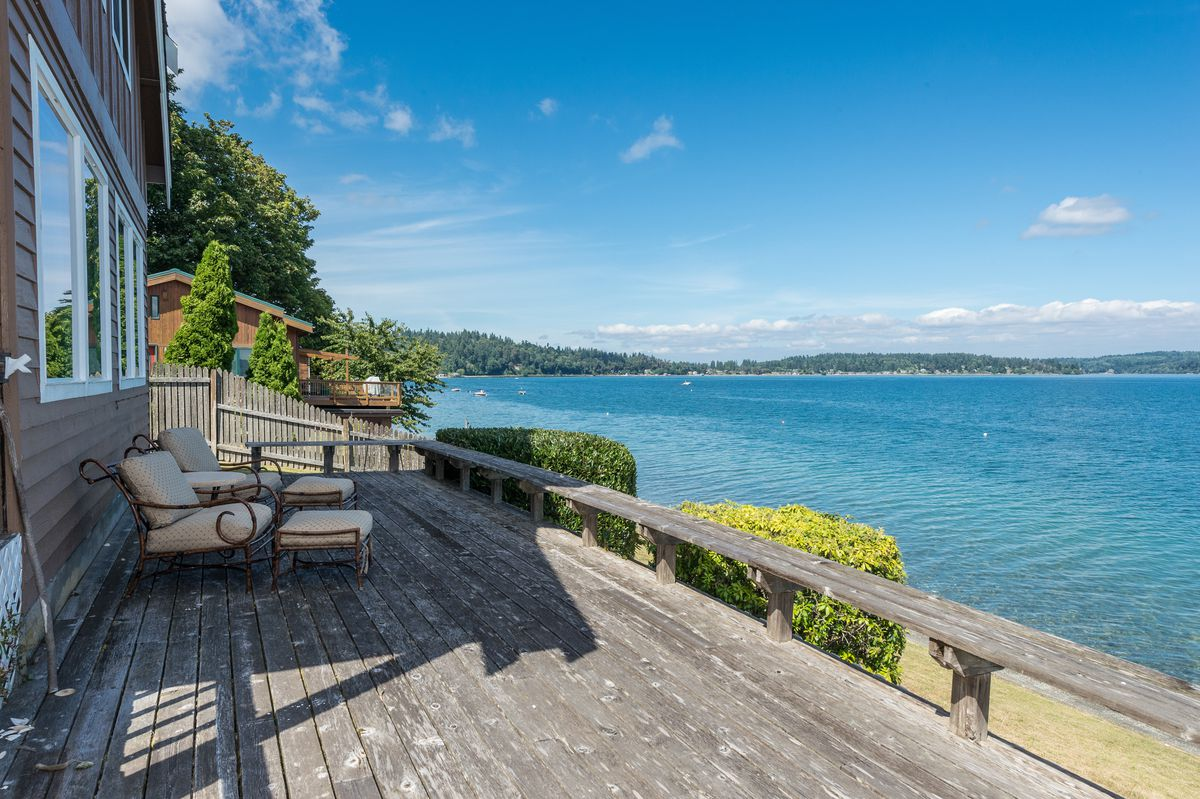 A wide, weathered wood porch overlooking the water.