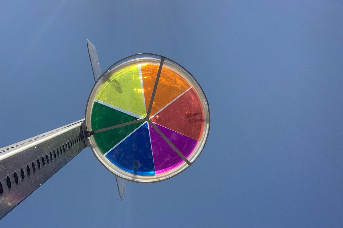 A disc filled in with multi-colored wedges, mounted to a street sign post