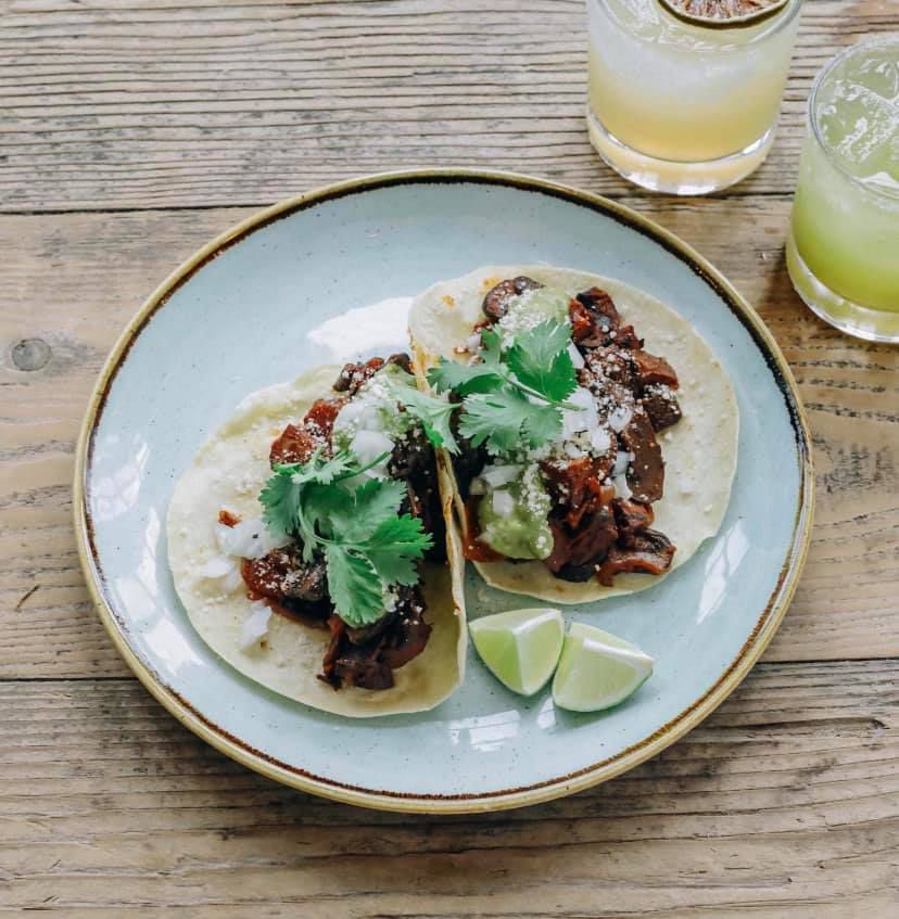 Two beef tacos topped with crumbly white cheese and giant leaves of cilantro on stoneware plates