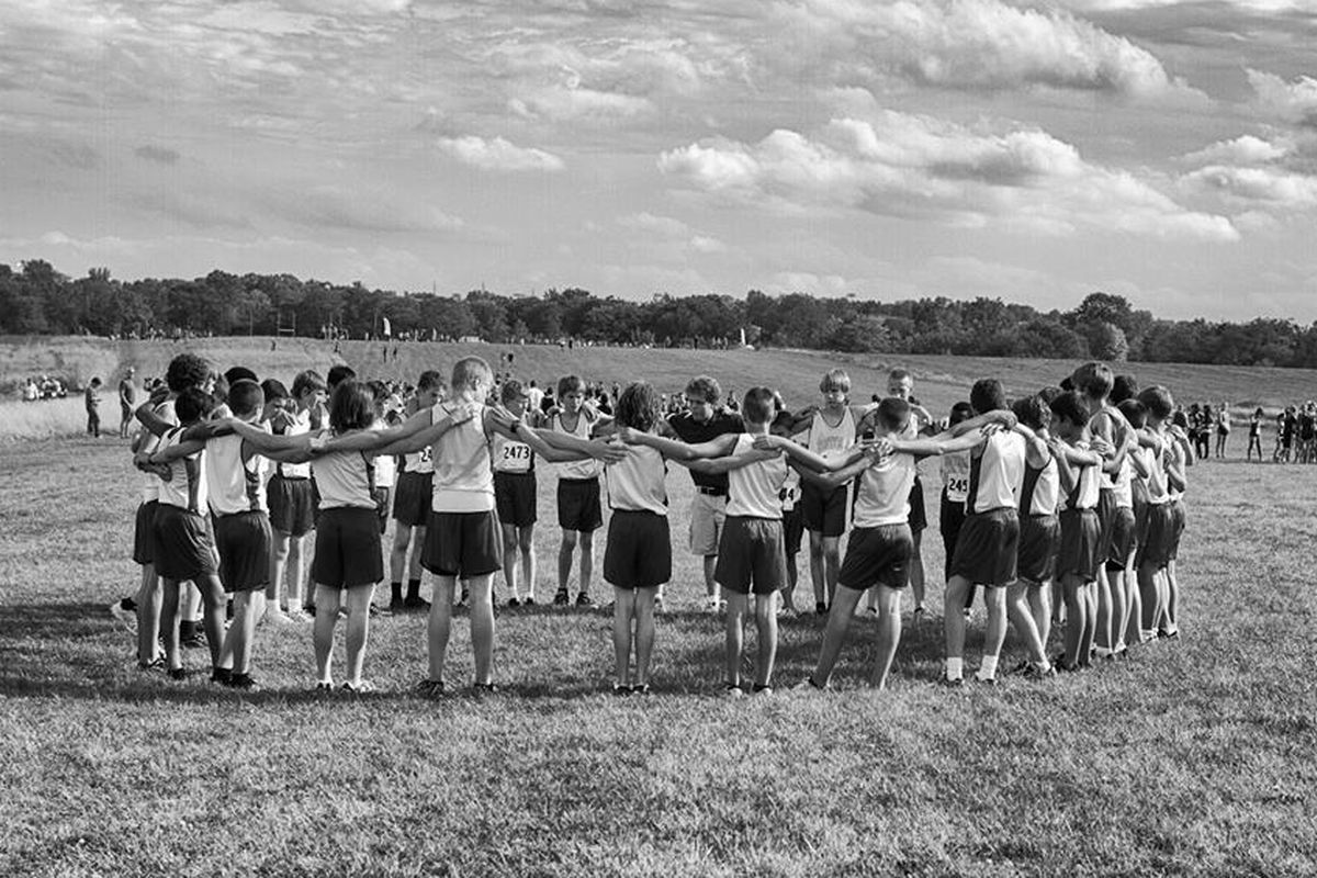 Coach Evan Risk huddles with his cross-country team.