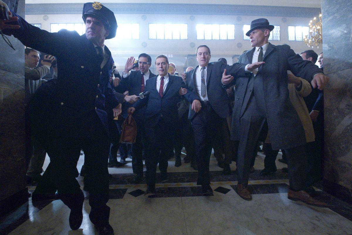 Bill Bufalino (Ray Romano), Hoffa (Pacino), and Sheeran (De Niro) fend off a crowd in The Irishman