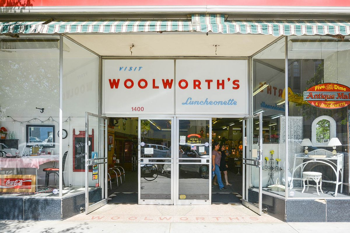 A daytime sign for a vintage Woolworth's store that has been converted to an antique store.