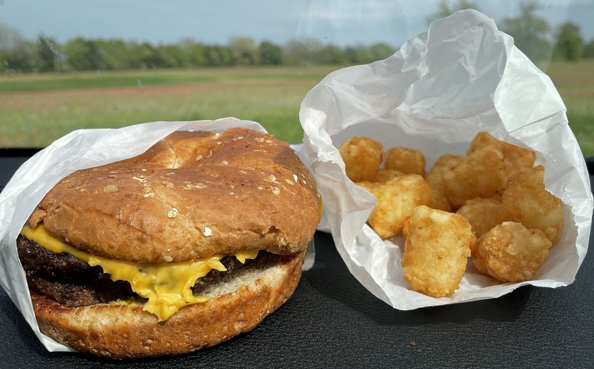 A bison cheeseburger and crispy tater tots, both wrapped in white paper. A grassy field sits in the background