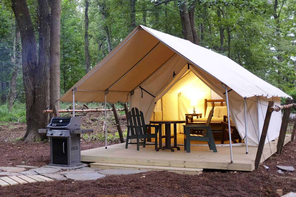 A white canvas tent is set up in a forest with poles and wooden seating as an example of glamping.