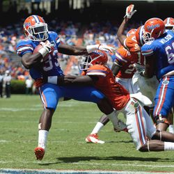 Florida's Mack Brown (33) pulls Jabari Gorman (21) with him as he scores a touchdown during th Orange & Blue football game  in Gainesville, Fla.,  Saturday, April 7, 2012. The Blue Team defeated the Orange team 21-20.