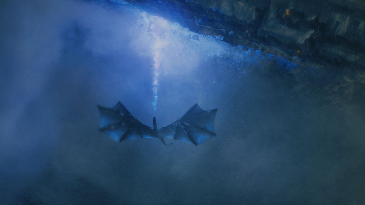 The Night King's dragon spits blue fire at the Wall on Game of Thrones.