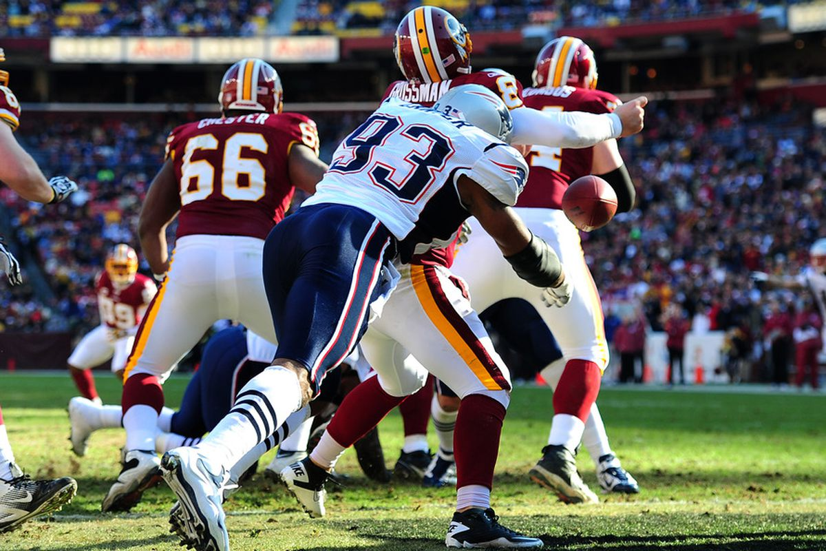 LANDOVER, MD - DECEMBER 11:  Rex Grossman #8 of the Washington Redskins fumbles as he is hit by Andre Carter #93 of the New England Patriots at FedEx Field on December 11, 2011 in Landover, Maryland. (Photo by Scott Cunningham/Getty Images)