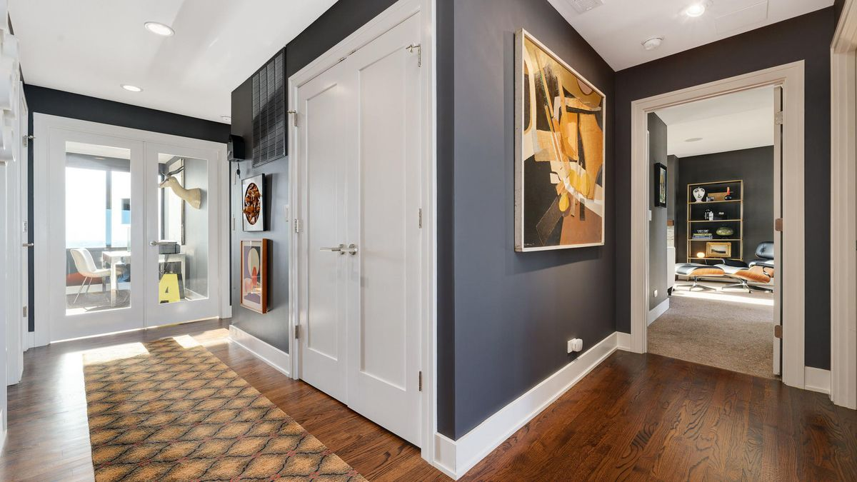 An L-shaped passageway with dark gray walls and artwork lead to a home office behind glass double doors.
