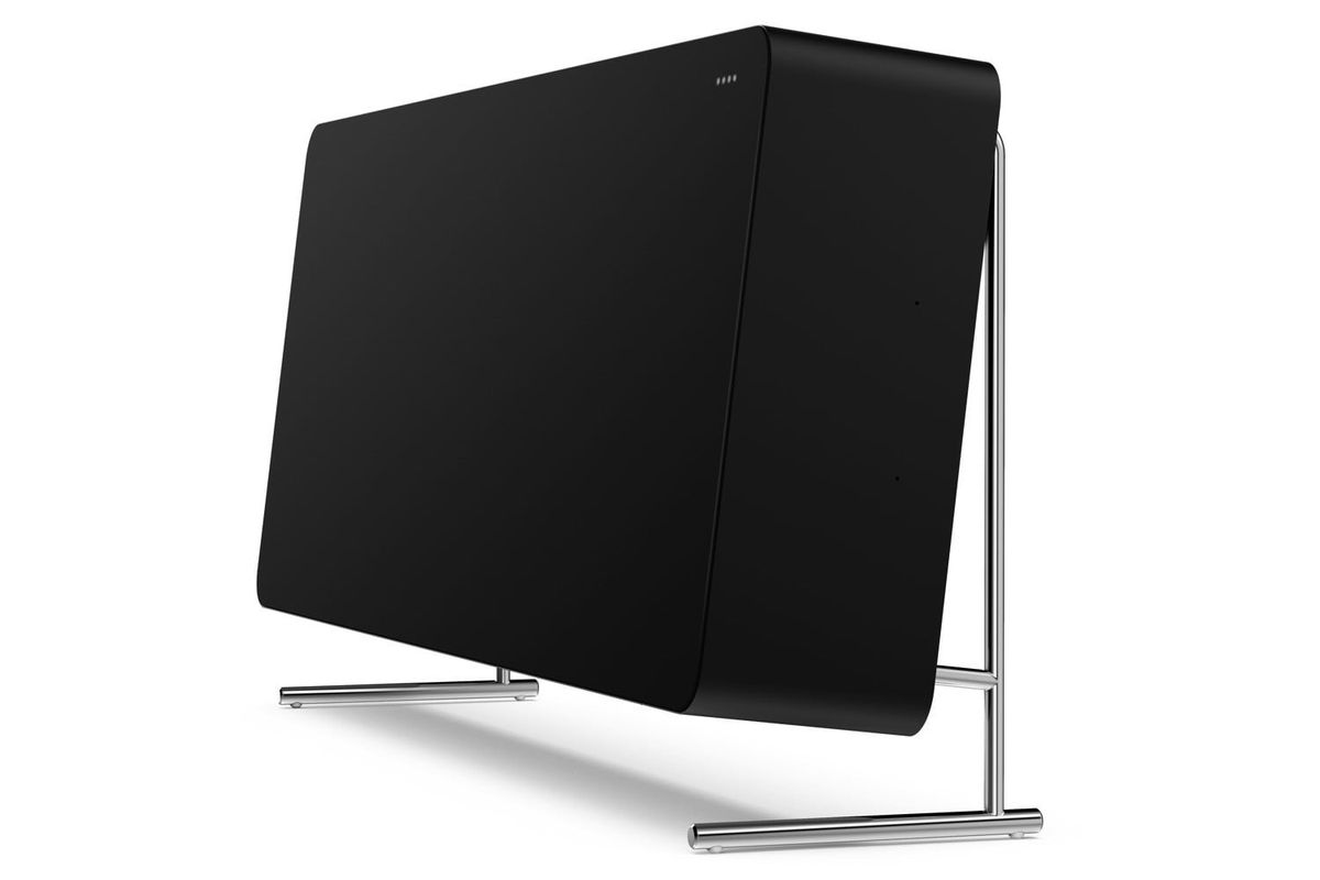 A side view of black speaker, with the speaker tilted slightly up and sitting on skinny silver legs and a back stand.