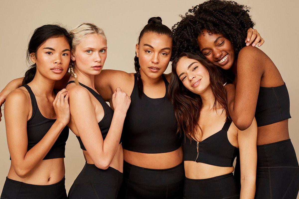 Five models wearing black sports bras and black leggings
