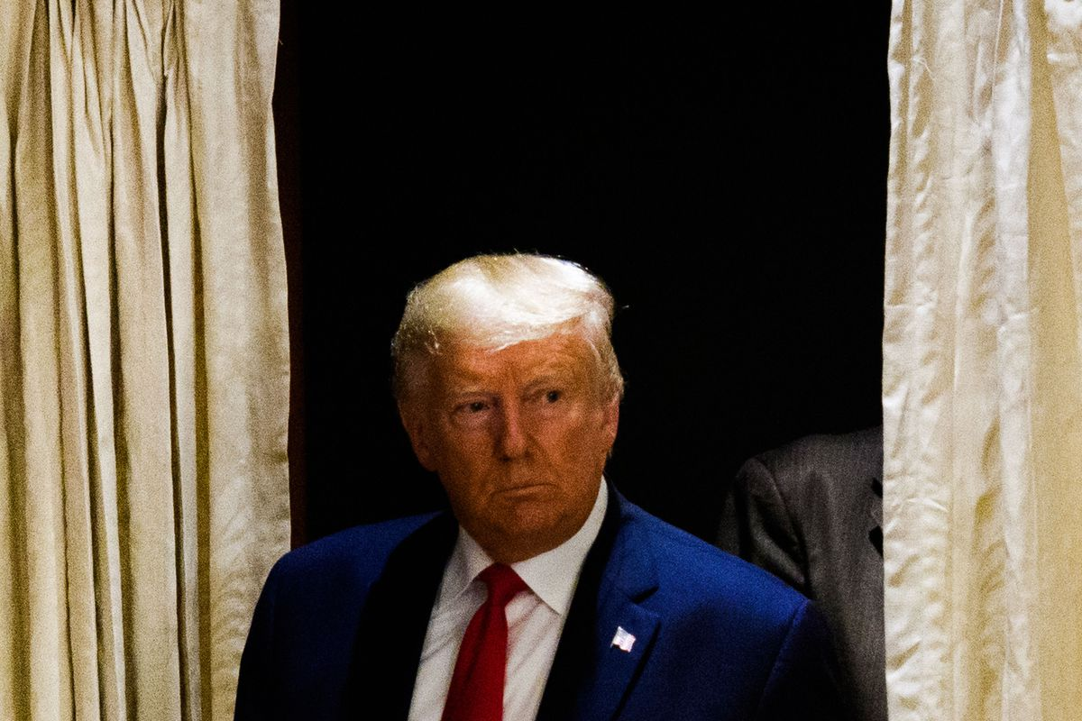 Trump, in a navy suit with a red tie, looks stern as he poses in front of gold curtains.