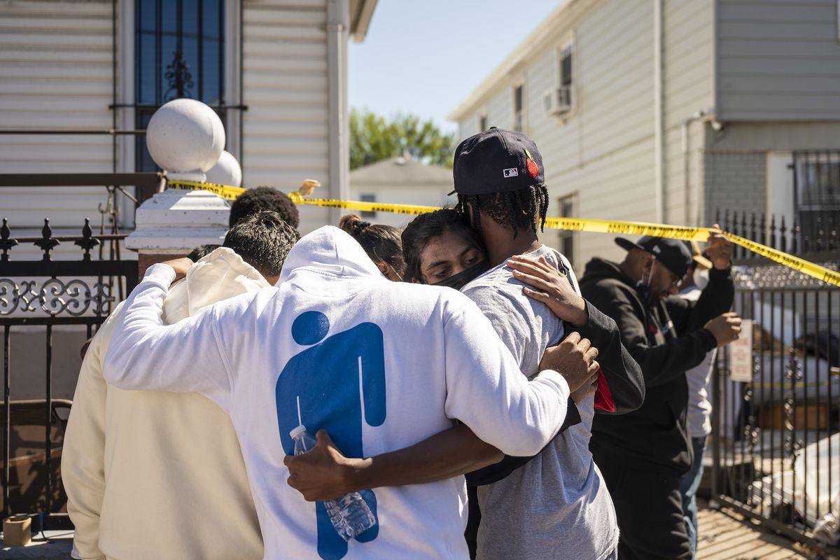Neighbors embrace one another outside of the Hollis, Queens, home where multiple people died during Wednesday night's flooding.