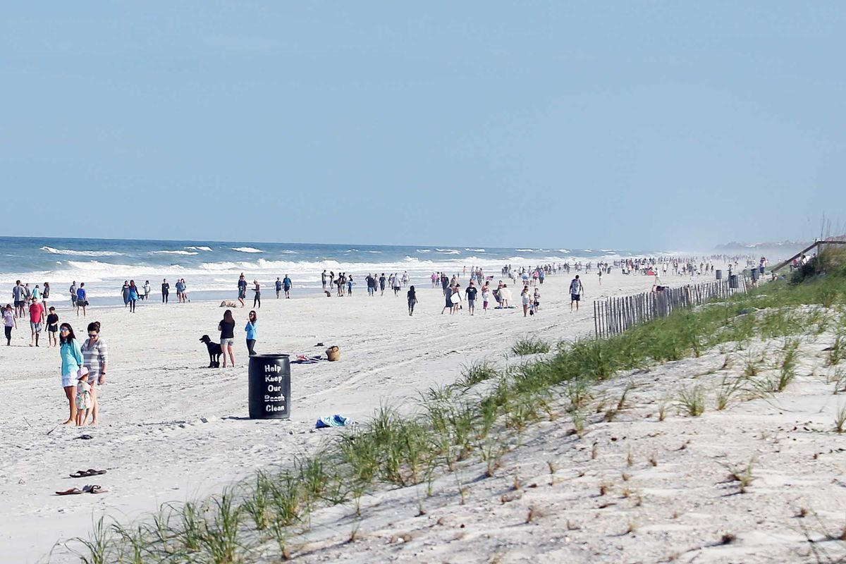 People mill about in small groups on a white beach. Some appear to be socially distancing. Others, not so much.