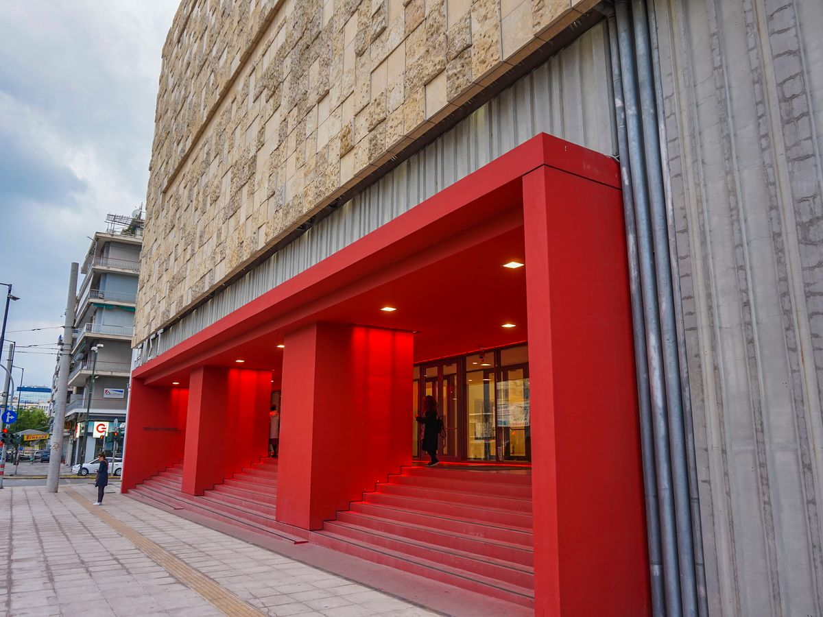 The exterior of the National Museum of Contemporary Art in Athens. The entryway has a red frame and steps. The building facade is tan.