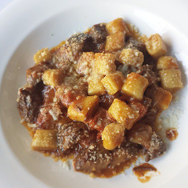 Overhead shot of gnocchi and a meat sauce on a white plate