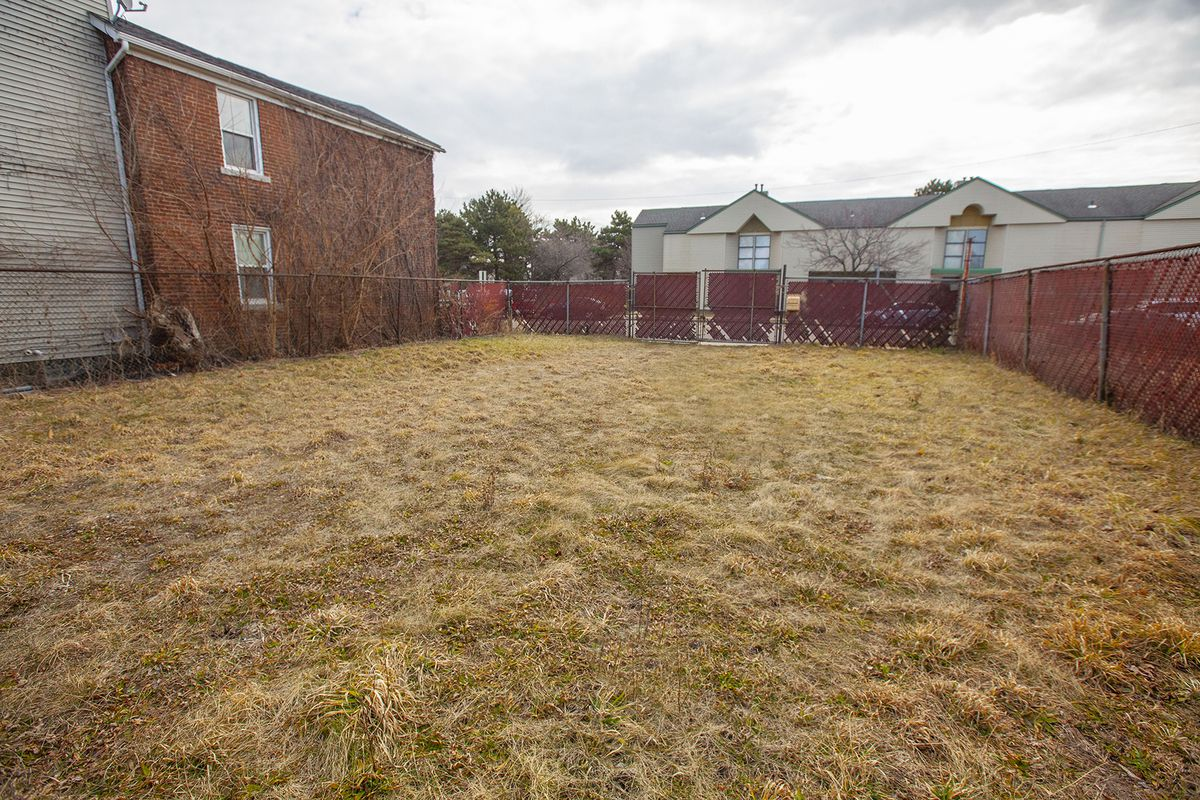 An empty, grassy yard surrounded by a metal fence with red mesh.