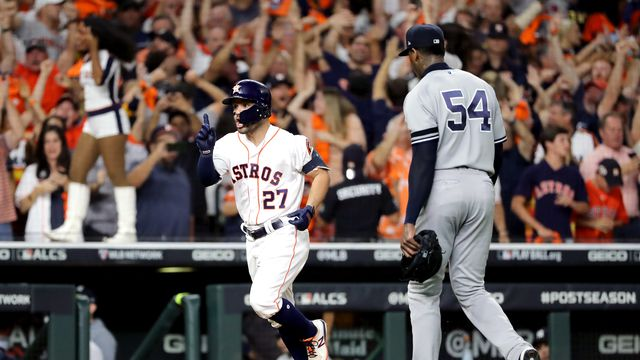 the Houston Astros' Jose Altuve trots toward home plate past the New York Yankees' Aroldis Chapman walking off the field as fans celebrate in the background