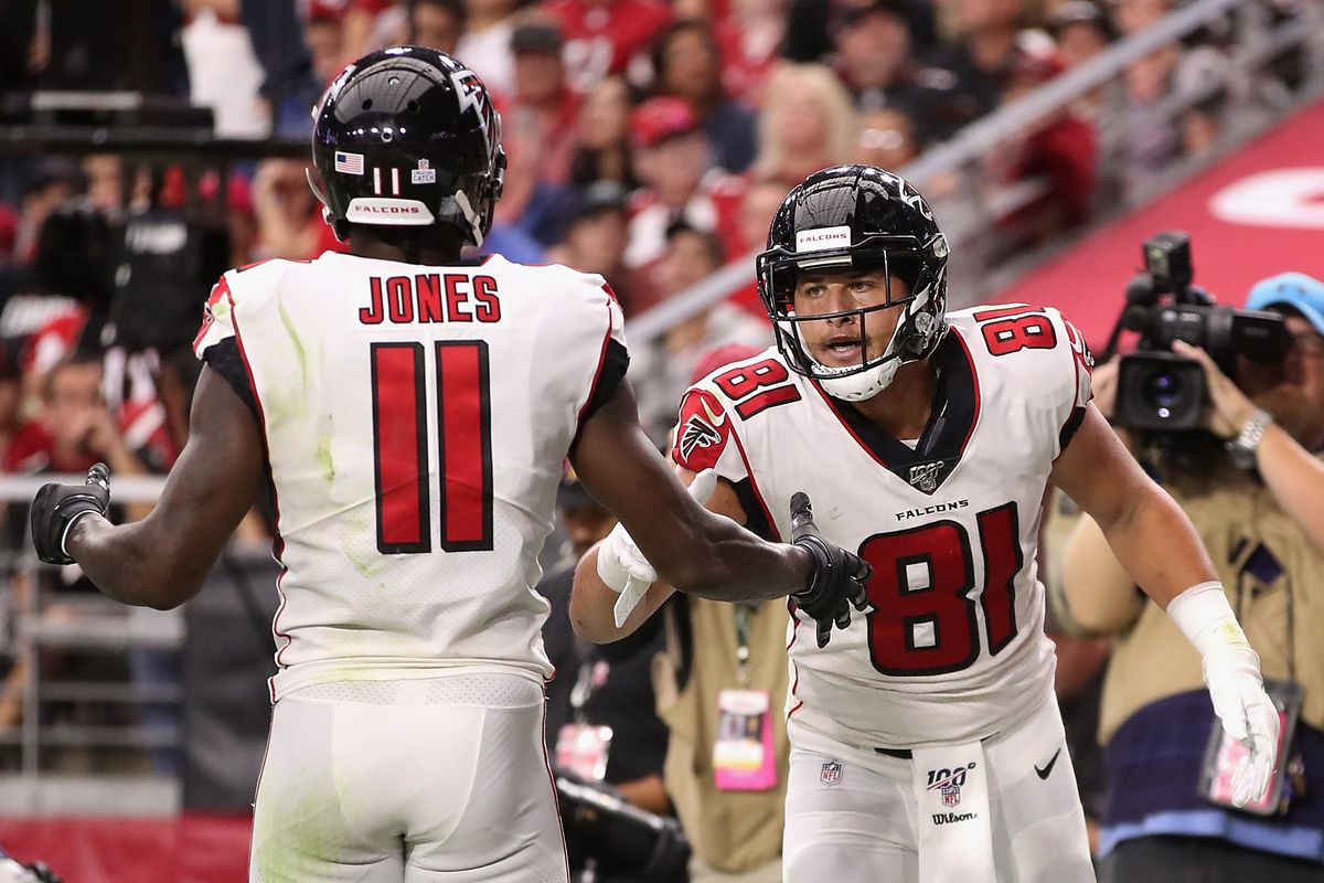 Tight end Austin Hooper of the Atlanta Falcons celebrates with Julio Jones after scoring a six yard touchdown reception during the second half of the NFL game against the Arizona Cardinals at State Farm Stadium on October 13, 2019 in Glendale, Arizona.
