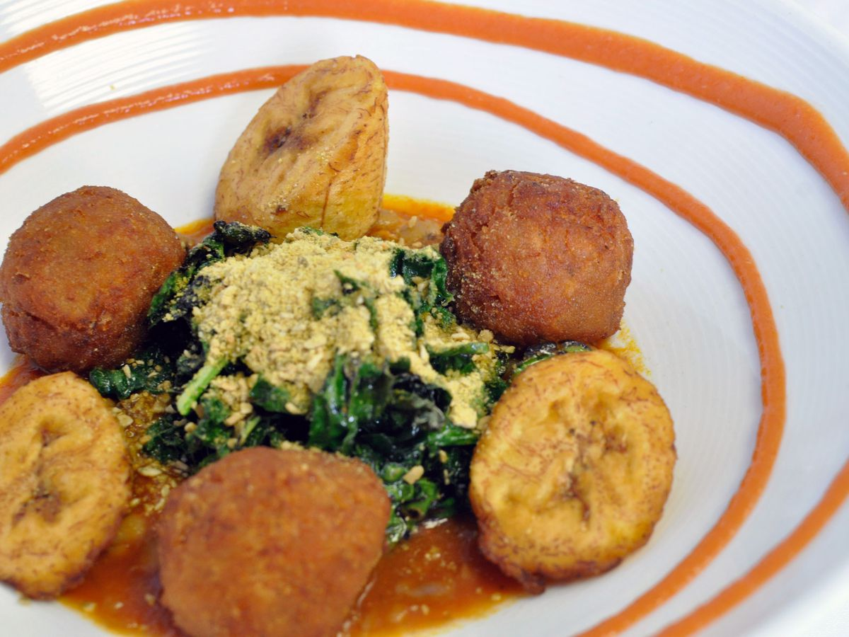 Closeup of a white dish with a pile of sauteed greens in the middle, sitting in a pool of red sauce. Arancini and pieces of plantain circle the edge of the plate.