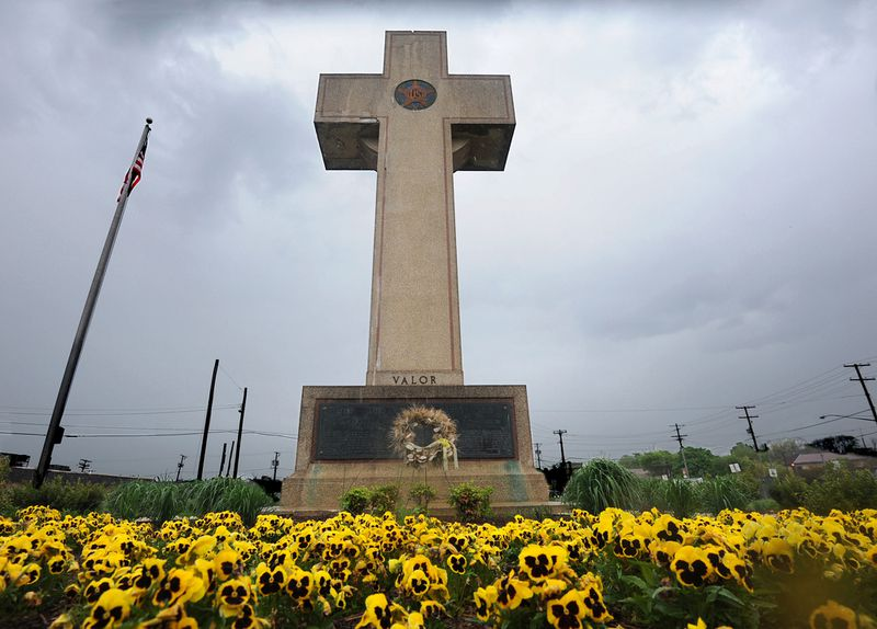 """The 40-foot-tall """"Peace Cross"""" war memorial with a field of pansies in front of it."""