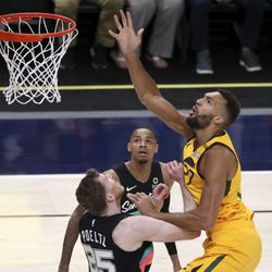 Utah Jazz center Rudy Gobert (27) shoots over San Antonio Spurs center Jakob Poeltl (25) and San Antonio Spurs guard Dejounte Murray (5) during an NBA game at Vivint Smart Home Arena in Salt Lake City on Monday, May 3, 2021. The Jazz won 110-99.
