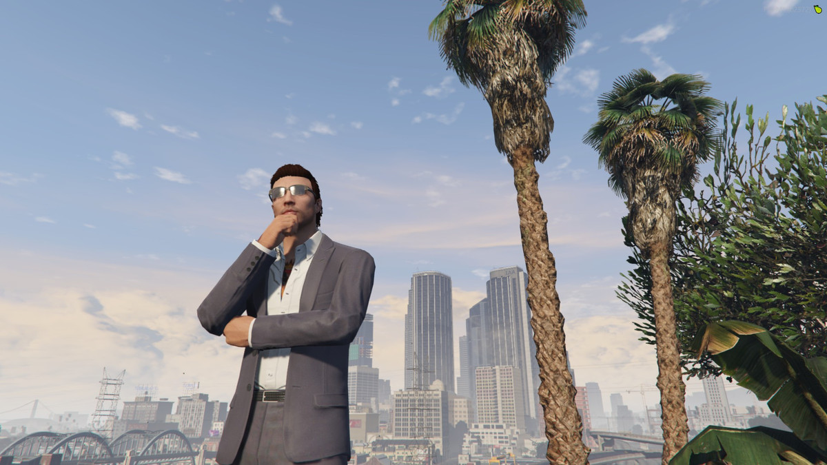 Grand Theft Auto Online - a man in a grey suit and sunglasses poses thoughtfully against the scenery of Los Santos