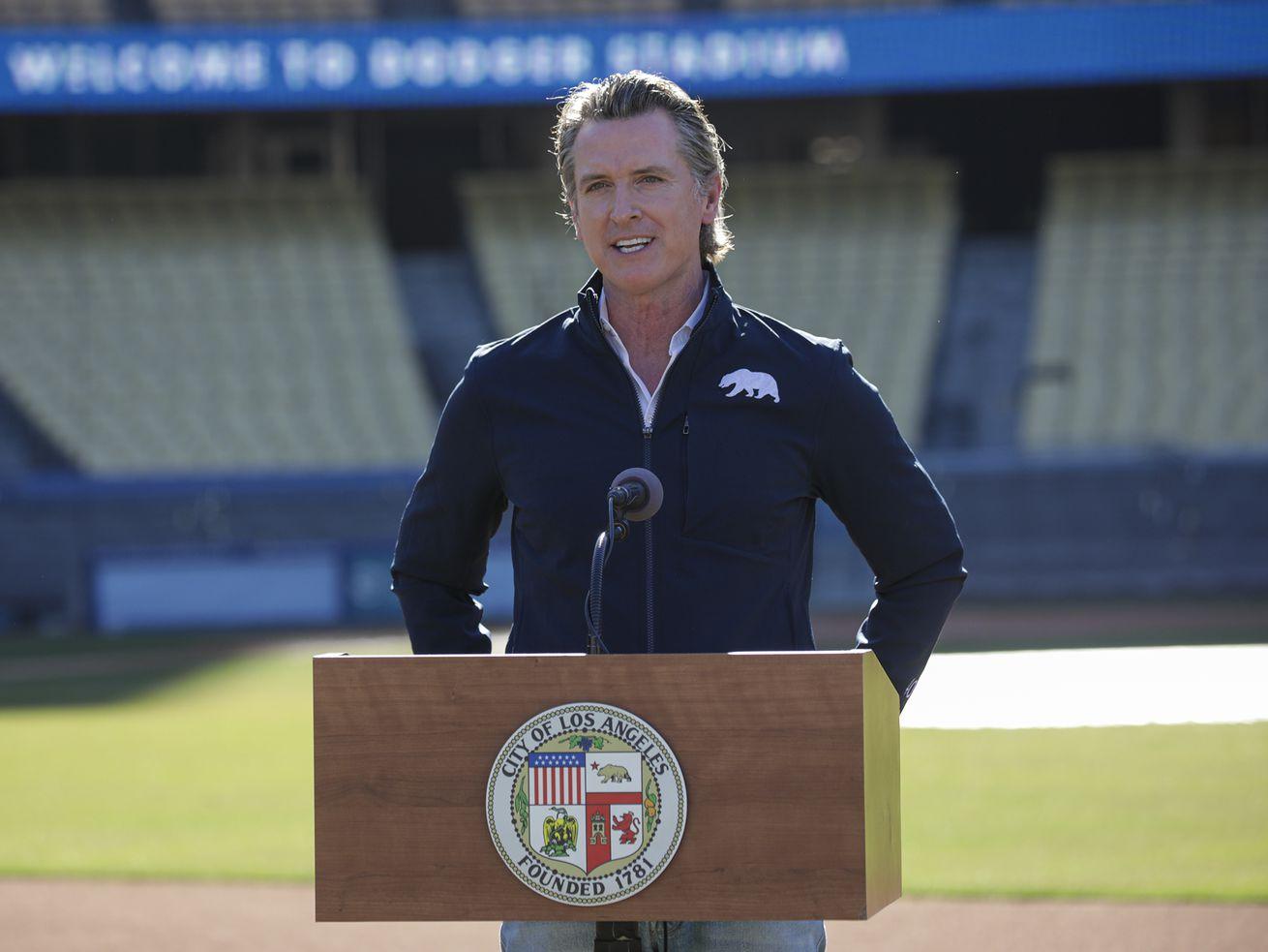 Gavin Newsom stands at a podium in Dodger Stadium.